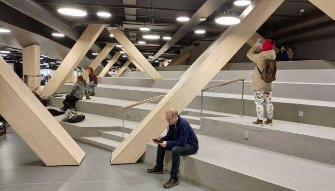 Большой амфитеатр с деревянными опорами служит местом для чтения общения и просто отдыха Центральная библиотека Oodi Хельсинки Фото strelkamagcom